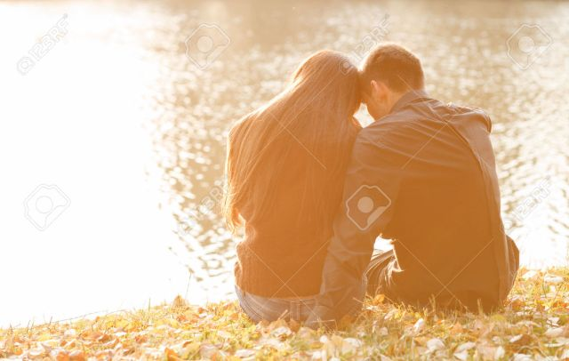 24714793-young-couple-sitting-near-lake-in-evening-heads-together-rear-view-Stock-Photo.jpg